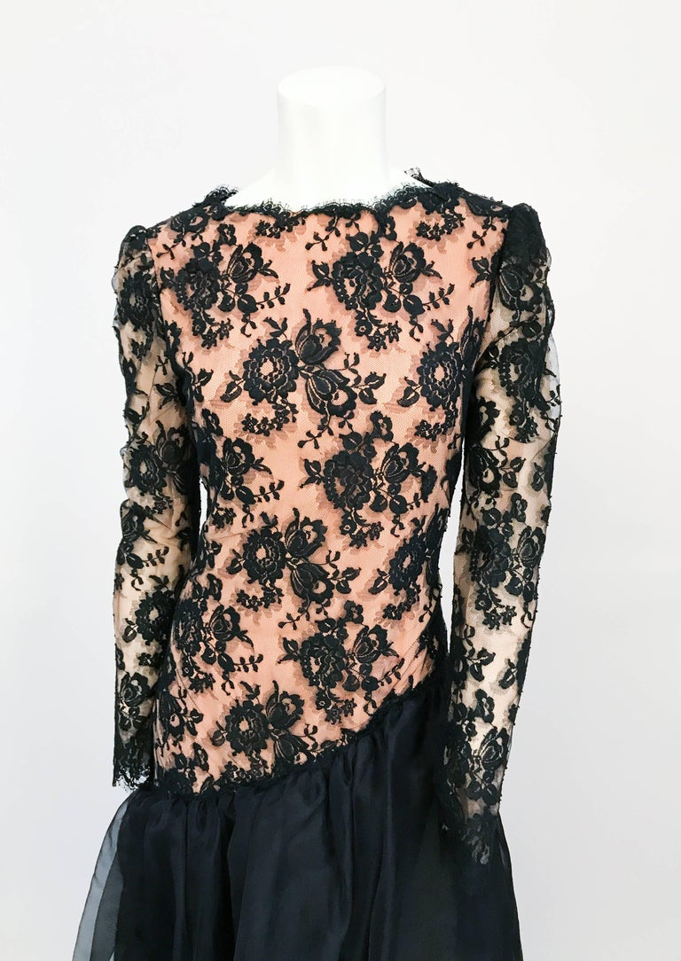1980s Travilla Black Floral Lace Dress. Black Floral Lace dress with full sleeves, drop waist, and black sheer flare. Peach color lining that can be seen through the black floral lace.