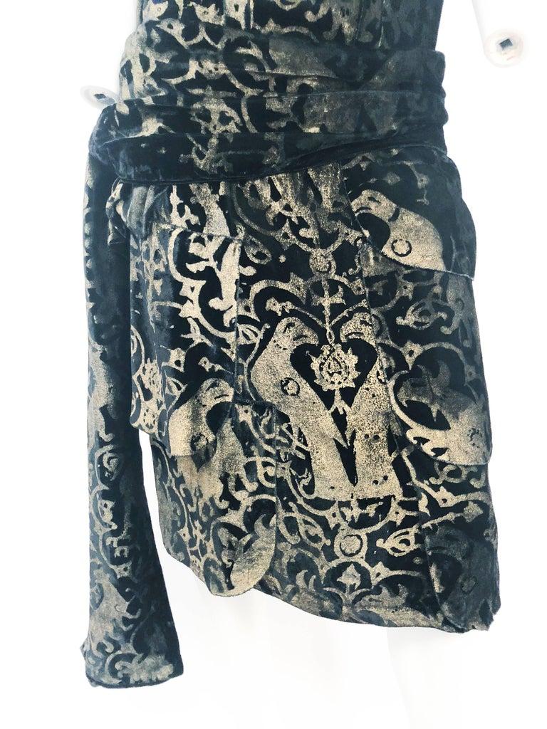 1920's Maria Gallenga Black Silk Velvet Dress with Hand-Stenciled Novelty print. Black silk velvet drop waist dress with gold pigmented hand stenciled novelty print with exotic birds and wild cats. Two-tiered peplum, padded shoulders, and matching