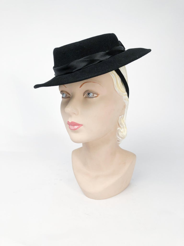 Black cashmere felt hat with hand-rolled silk satin band, layered bow, and rhinestone accent (black and clear rhinestones). Felt hat band with elastic attachment to further secure the hat to the head.