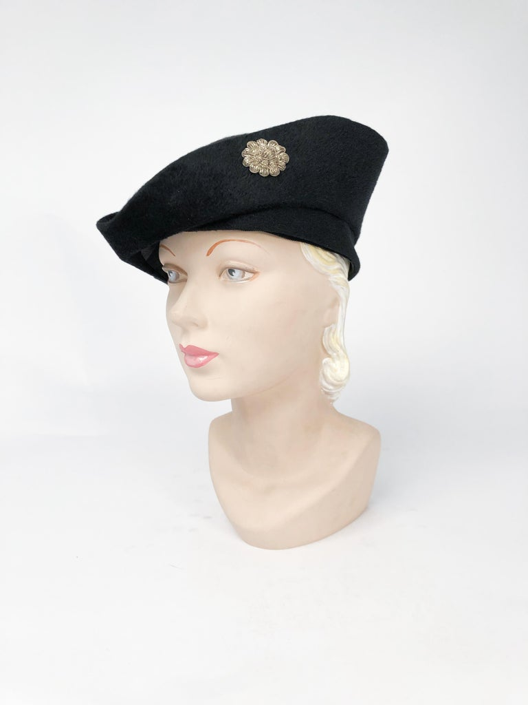 1930s Black cashmere felt hat with traditional pirate shape. Sterling Silver flower accent on the side of the brim.