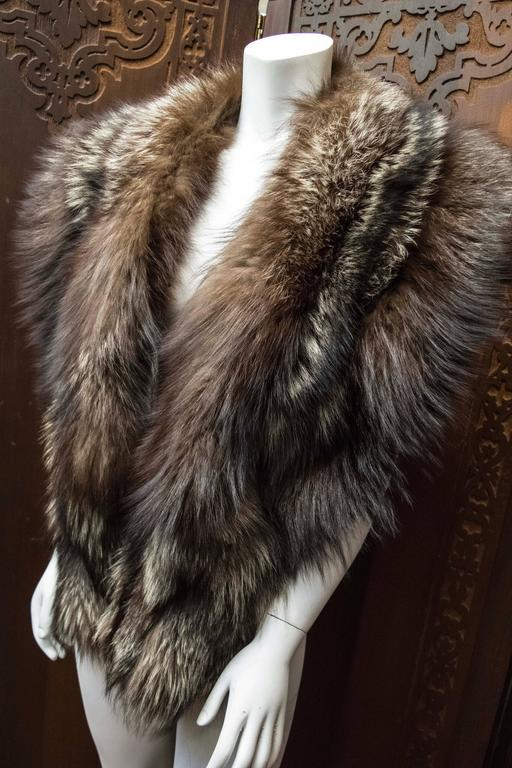 Silver Fox Fur Wrap  This luxurious silver Fox fur wrap is soft, long, and fluffy with a stunning lamé lining. The fur has retained it's supple skin and the underfur, guard hairs remain soft, dense, and fluffy. The piece has fur clasps in the