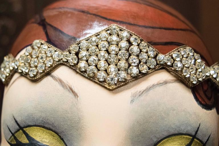 Stunning early 1920s headband beautifully preserved, and unused since the 1920s, stored in original box. The piece has Swarovski crystals in a brass filigree weave.  Wonderful piece of Art Deco history.