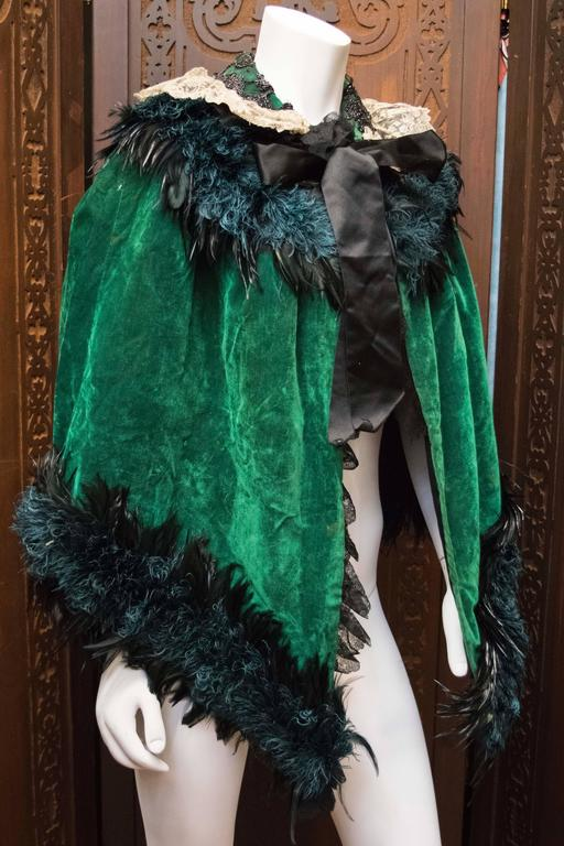 Green Velvet Victorian Cape  Fantastic piece of eccentric Victorian fashion history, this green velvet cape has lace detailing, and ebony rooster, and dyed, hand curled Marabou feathers.   L 30 W 36