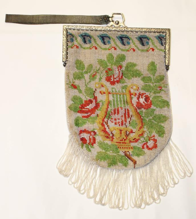 1920's hand-beaded purse with green leaves, red roses, and harp against a white field in seed beads. Blue flowers border the top edge. Silver tone embossed frame. Unlined. Looped seed bead fringe. Mesh wristlet.