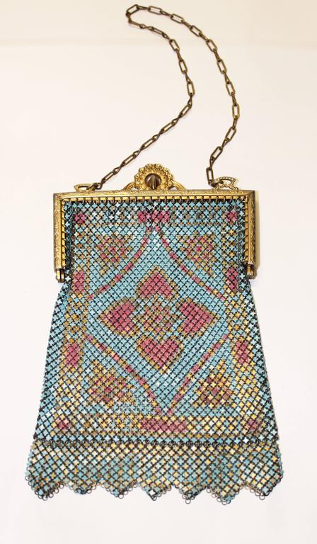 """1920's painted bright blue and pink mesh purse with floral design. Zigzag mesh panel fringe and ornate gold tone frame. Elegant metal chain handle.  Measurements: Handle: 12"""" long Length: 6"""" long including mesh fringe Width: 4"""""""