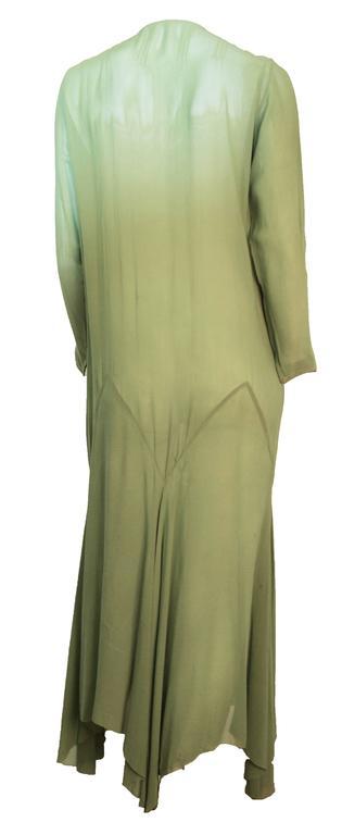 20s trompe l'ceil long sleeved moss green chiffon dress with a handkerchief hemline. Beaded trim along front neckline.