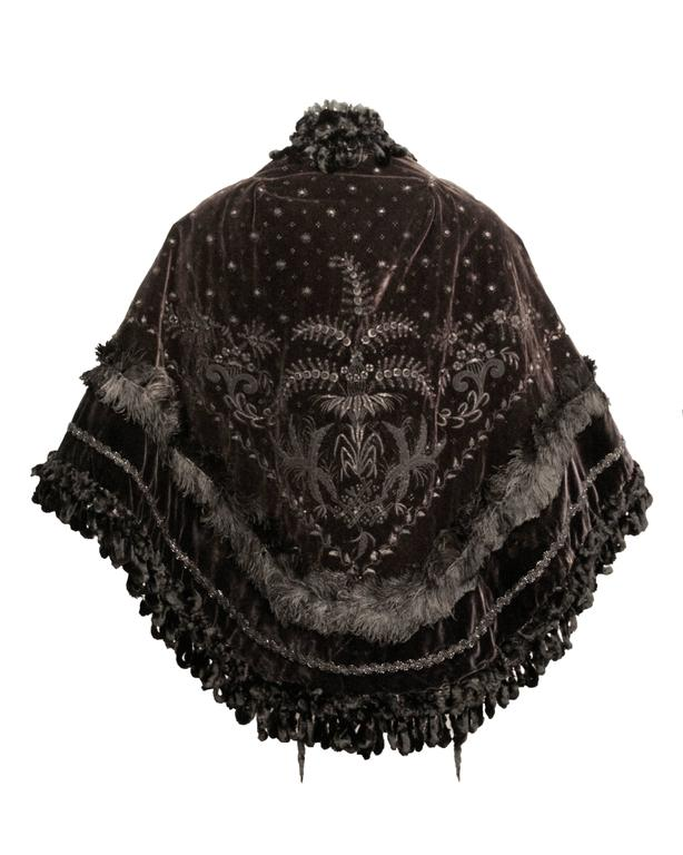 Victorian velvet cape with beaded appliqué and feather trim. Chenille trim along neckline and hem of cape. Hook and eye closures along front opening. Quilted silk lining.
