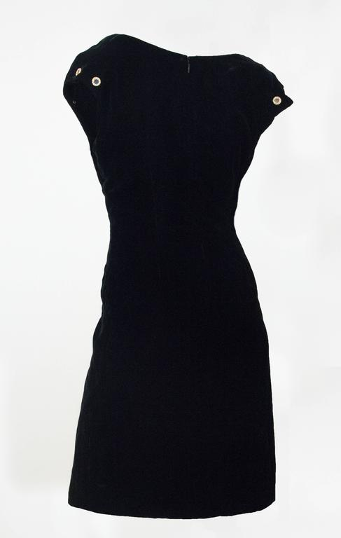 90s Christian Lacroix velvet sheath dress. Gold tone rhinestone encrusted grommets on cap sleeves. One inset pocket on left front. Fully lined. Zips up the back.