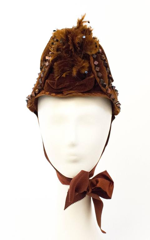Victorian Brown Velvet Bonnet. Feather and copper colored stud embellishment. Satin ties. Lined.