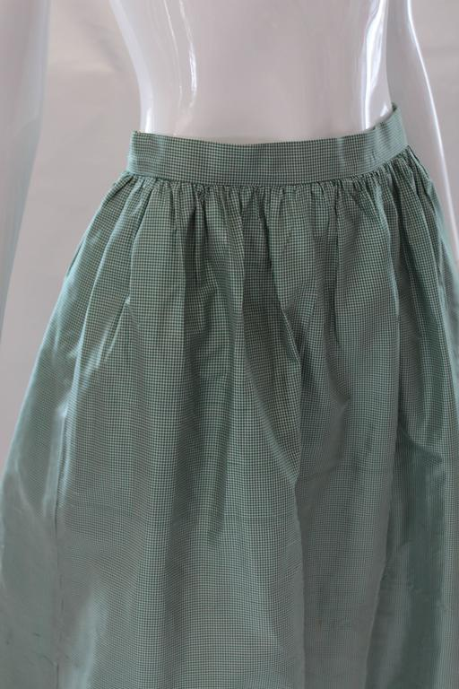 The gorgeous ball skirt of micro gingham silk taffeta features gently gathered waistline, full skirt, pockets and generous ruffle.  Would be pretty styled down with crispy shirt. Measurements in inches... Total Length: 43 Waist: 27 Hips: 56