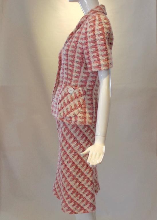This Bill Blass pink tweed women's suit is the perfect vintage addition to any wardrobe. The short sleeve blazer has a two-button closure, pockets at the waist and is paired with a flirty a-line skirt that falls at the knees. Skirt includes a