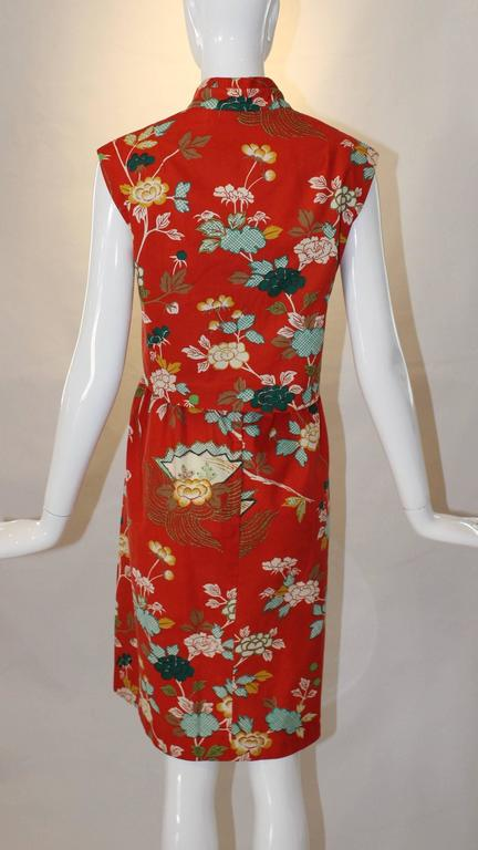 This adorable printed 1960s Two Piece Sundress Set from Neiman Marcus is right on trend, even fifty years later! A red, blue and yellow floral print decorates this adorable dress and a Mandarin collared cropped topper finishes it off. 