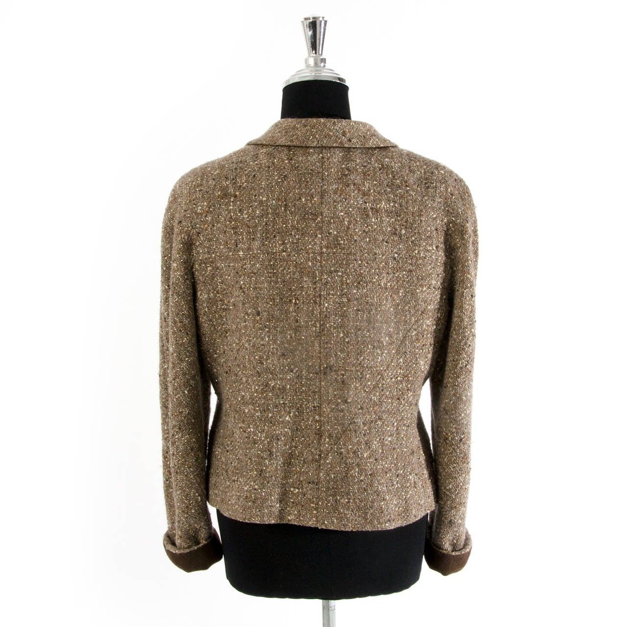 There is nothing quite as iconic as a classic Chanel tweed piece. Short brown  Chanel jacket. Made from famous Bouclé wool tweed with brown checked pattern. Some specks of gold , creme and beige throughout the tissue. Brown Silk lining.