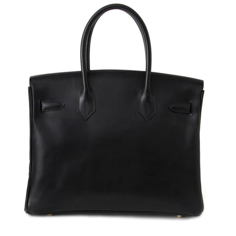 Hermès Black Birkin bag in Box Calf leather.  This beauty is made of smooth and glossy calf skin that is more rigid than the grainy leathers, the box calf leather develops a highly desirable patina over time.   Blind Stamp E in a square