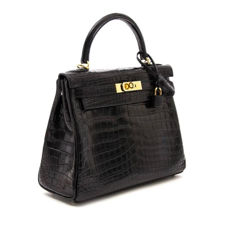 Extraordinary Hermès Kelly bag with strap, in matte crocodile niloticus. Niloticus Crocodile is considered by many to be the premier Hermès skin. It is characterized by a symmetrical scale pattern and denoted by the inverted v symbol next to the