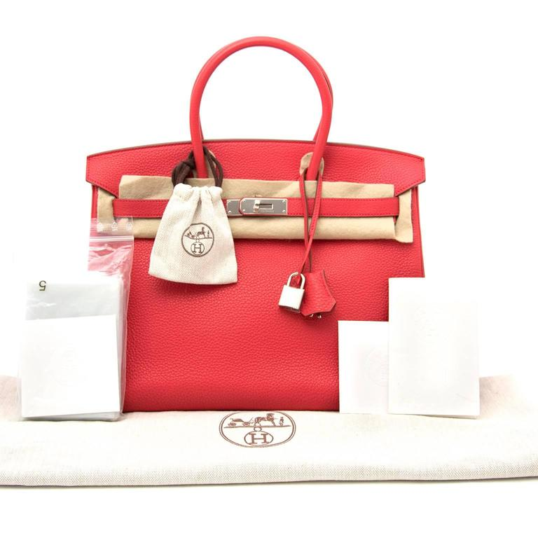 Brand New gorgeous and eyecatching Hermès Birkin bag, measuring 35 cm, handcrafted from supple Clemence Taurillon calfskin.  Its charming and playfulcolor, named by Hermès 'Rouge Bougainvillier' , a lovely red with a touch of pinky undertone. The