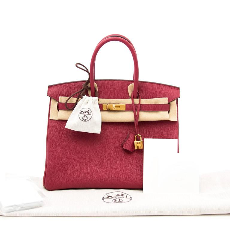 Store Fresh Hermès Birkin bag in timeless warm red 'Rouge Grenat' with matching gold-tone hardware. The Togo leather is soft to the touch and the fine grain gives theh bag a luxurious allure. Never worn, straight from the store! I  Comes with: