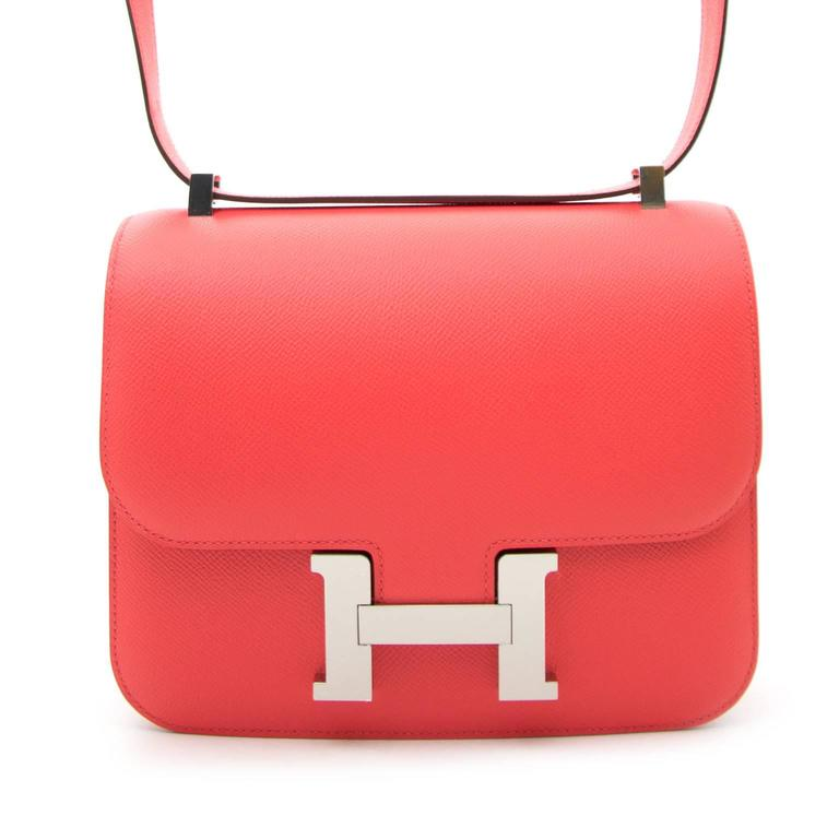 BRAND NEW Hermès Constance 24cm Epsom Rose Jaipur  This store fresh bag is finely crafted from epsom calfskin leather in a bright coral pink with palladium silver hardware including a H buckle at the front.  This item makes your outfit fresh and