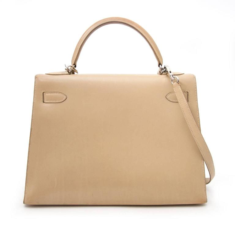 Very Good Condition  Hermes Kelly 32 Poussière Box Calf + Strap  The iconic Hermes Kelly made out of boxcalf leather in a soft beige color with silver harware. Hermès boxcalf leather is very smooth with a glossy finish, and a structured hard leather
