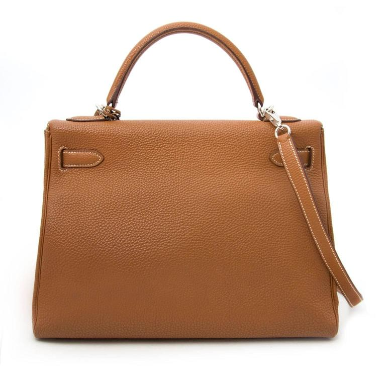 Hermès Kelly 32 Togo Gold PHW  This Hermès Kelly comes in a smooth and grainy gold togo leather. This is a real statement piece.  The Kelly bag features palladium silver hardware which makes the gold tone pop!   Comes with      Dustbag