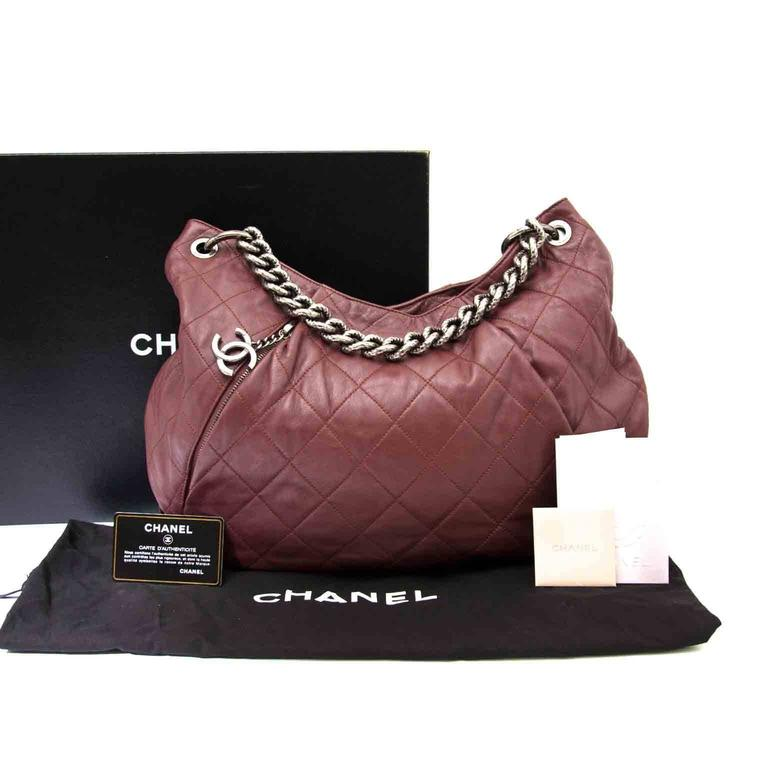 In very good condition  Smooth burgundy leather hobo satchel by Chanel. Adges ruthenium hardware and CC hang lock zipper on the front part.  This bag can be worn as a shoulder bag, crossbody, or by hand thanks to the two straps. The leather strap is