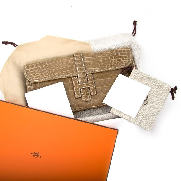 """This Hermes Jigé Elan Clutch Bag comes in beautiful Ficelle Crocodile niloticus.  Shiny Niloticus Crocodile, has a somewhat larger scale pattern than Porosus croc. It is shiny and only the very finest skins are used; the """"lisse"""" finish"""