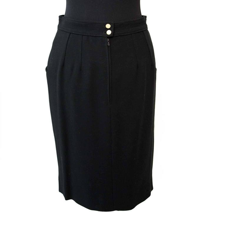 Very good condition  Chanel Black Woolen Skirt - Size: 38  This classic piece of Chanel comes in a neutral black color. Made out of 100% wool and a silk interior lining. The skirt is finished with a zipper closure and two gold-toned buttons in the