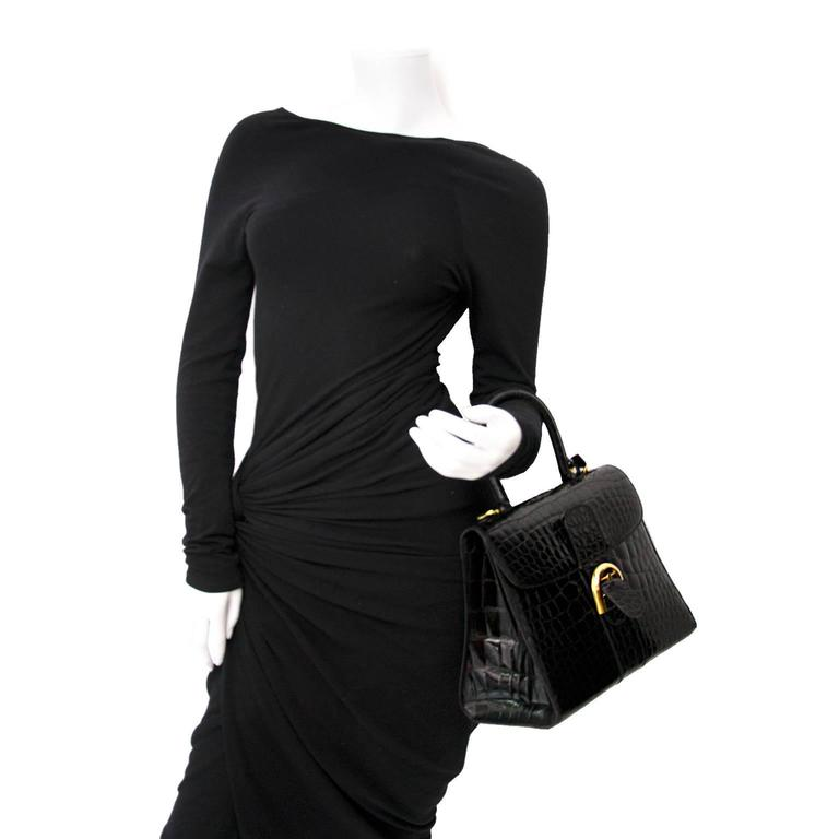 Good condition  Delvaux Black Croco Brillant MM  Estimated retail price: €28000   This iconic Delvaux bag comes in black shiny croco leather with gold-tone hardware. The front flap contains the classic horseshoe belt buckle to open the bag. On the