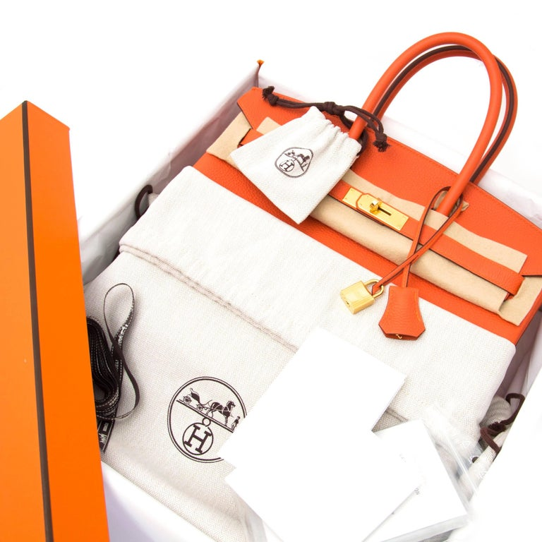 This highly coveted Hermès Birkin bag comes in the color Feu. It is even brighter than the 'Orange' color of Hermès. The bag is a bright pop of color!  The gold-toned hardware stands out beautifully. The popular Togo leather is Hermès' most wanted