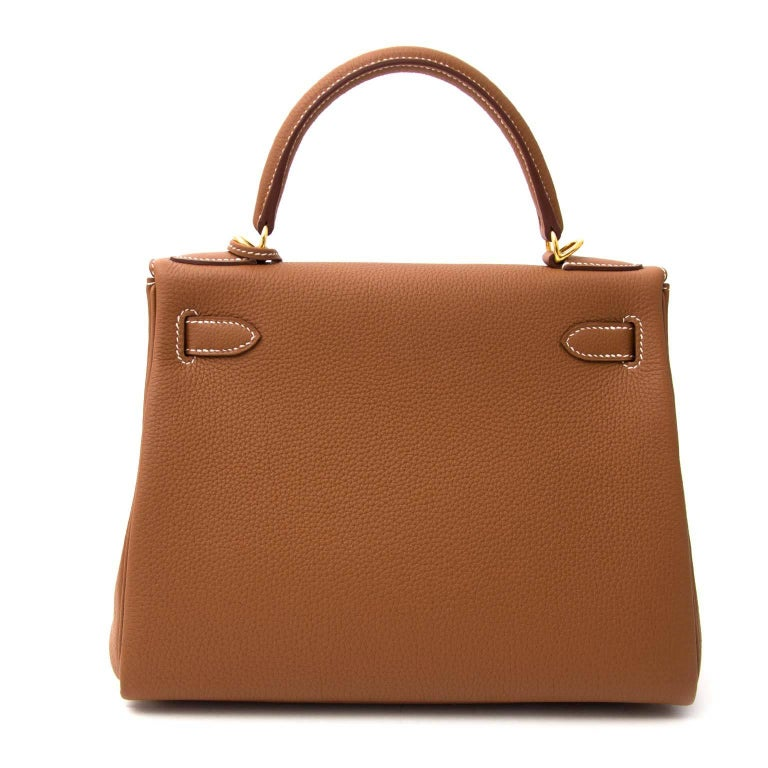 Never Used!  Hermès Kelly 28 Togo Gold GHW  This Hermès Kelly in timeless gold is a real statement piece.  The Kelly bag is made out of togo leather which is almost entirely scratch resistant and its grainy smooth texture is very nice.  The gold