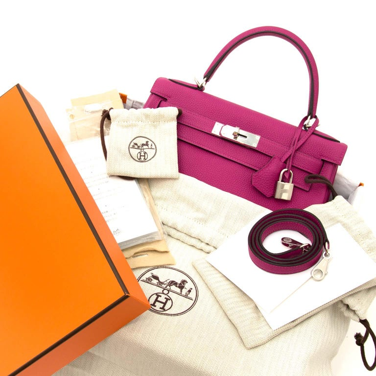 This stunning and eyecatching Kelly bag by Hermès comes in 'Rose Pourpre' Togo leather which is a deep and vibrant purple color.  Togo is a grainy yet smooth leather which keeps its form very well. It's also almost 100% scratch resistant.  Be unique