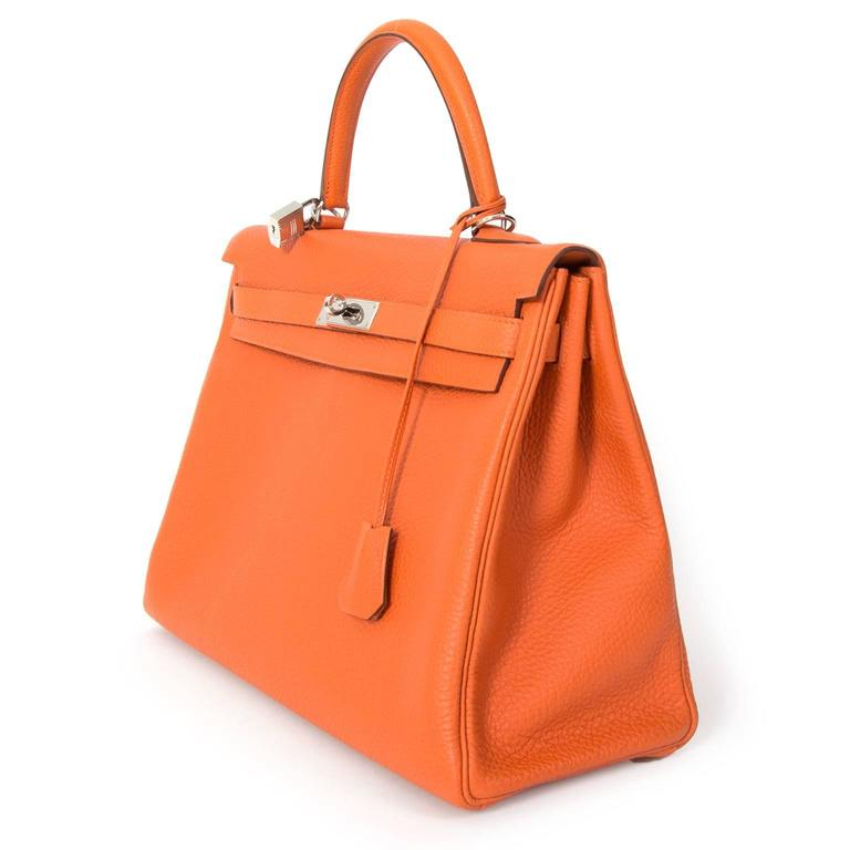 Brand new Hermes Sac Kelly Orange Retourne 35 Veau Togo in a bright orange  hue. c5aeabc37968