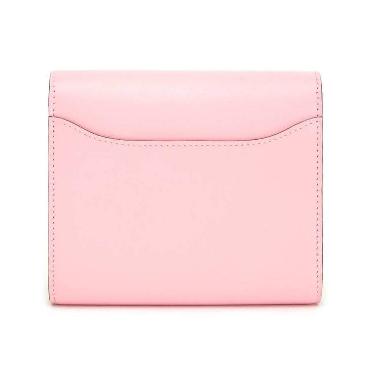 Store fresh Hermes Constance Compact wallet in baby pink. The stunning item contains two compartments and a zip pocket. Exterior features patterned pink Hermes 'H' as a closure and a slip pocket on the back. 