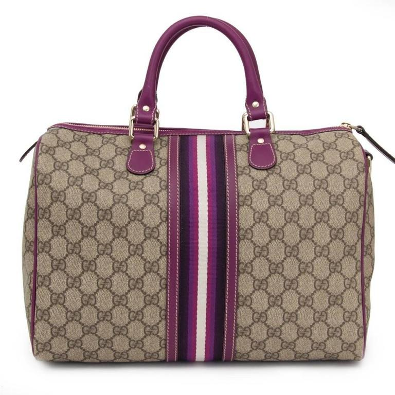 This Gucci Joy Boston with purple details is one of a kind. The bag is finely crafted of GG monogram canvas in cowhide leather and detailed with purple trim and rolled top handles. The interior is accessed through a golden zipper and contains a