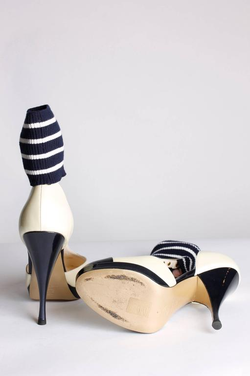 This pair is very special, Chanel pumps with a cuff around the ankle. Nice!  Made of patent leather in champagne cream and dark navy blue. A strap across the foot that holds a cuff. This knitted ankle cuff is striped in navy blue and white. An