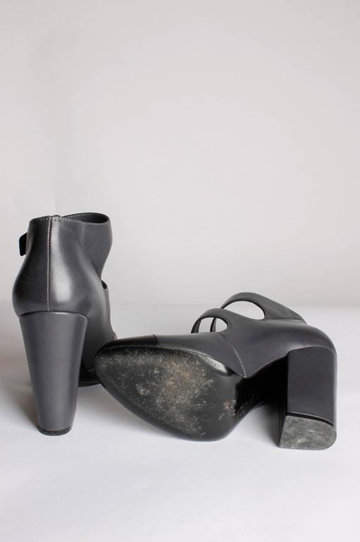 Dark grey leather pumps by Chanel, two straps and silver buckles. Sturdy!