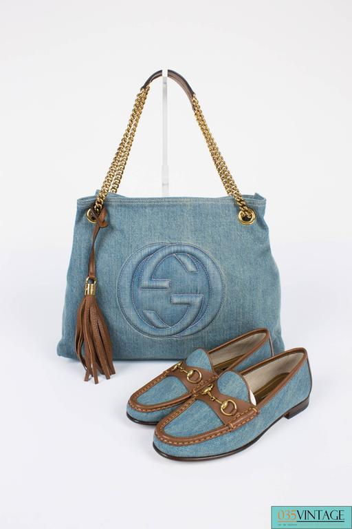 A blue denim bag by Gucci with brown leather trim and gold-tone hardware, a careless beauty!  This Gucci Blue Denim Medium Soho Tote Bag is fully crafted in light blue denim, a frontal stitched interlocking GG logo and the interior is lined with