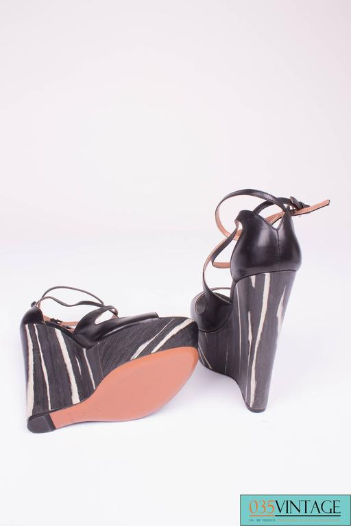 Summery wedges by Alaïa in black leather and a platform made of wood in black and white.  A crossed strap on the instep and one around the ankle. Small buckles in blackish silver. On the inside lined with nude colored leather, Alaïa Paris