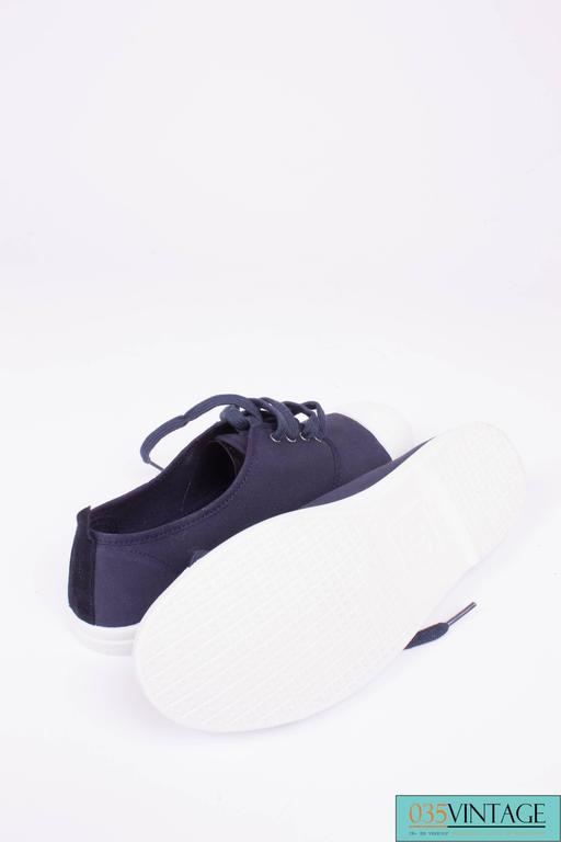 Sneakers by Chanel in dark blue canvas with a white rubber toe and sole.  A lace on the front and a white CC-logo on the tongue of the shoe. A dark blue CC logo on the toe. Heelheight 2 centimeters, lined with dark blue canvas.  New and never been