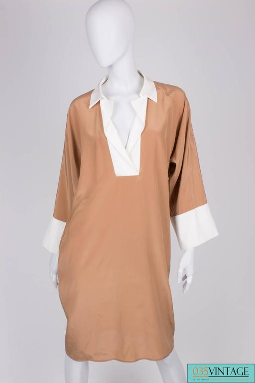 Camel colored dress by Salvatore Ferragamo with white detailing.  This supple dress with matching waistband has kneelength, a white collar and white cuffs. Welt pockets in the seam on hip heigth. No lining.  New! The tag is still on it. Original