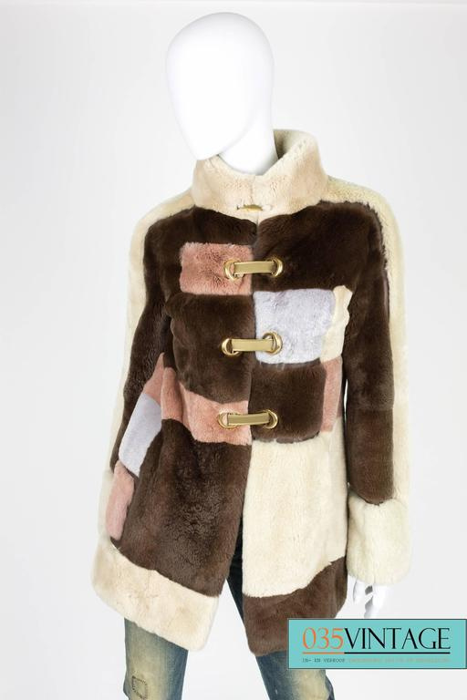 Supple and light fur coat with leather detailing by Emilio Pucci in a beautiful square pattern.  The squares are dark brown, beige, gray and pale pink. In between the squares you will find dark brown leather parts. Mandarin collar and welt pockets.