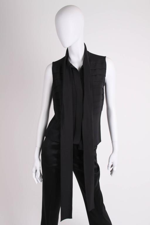 Elegant sleeveless blouse by Chanel in black silk, an oldtime classic!  This blouse has hip length and button closure up front. Eight stitched horizontal pleats in the upper part on the front and back. The collar is a rather long and wide ribbon of