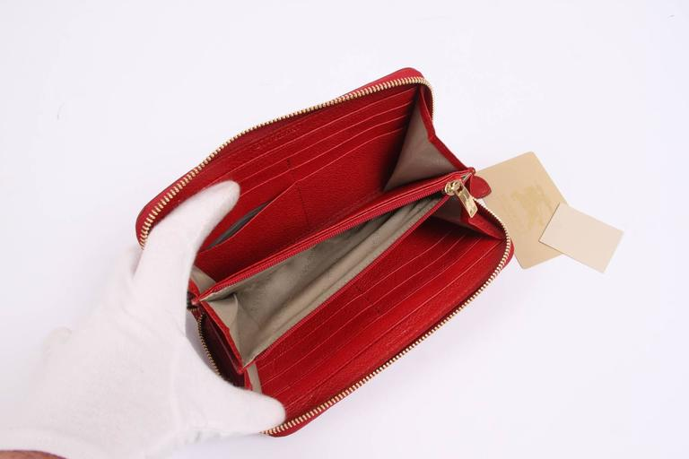 Brand new Burberry zip around wallet with the famous and welknown checkered look.  The exterior is made of synthetic material, trimming ini red leather. A gold-tone zipper on top. Interior lining with red leather. Three compartments, the center one