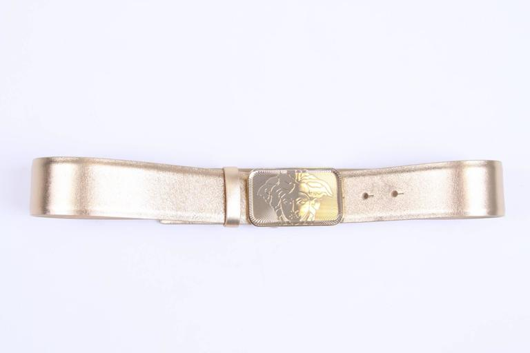 Brand: Versace  Material: gold-tone leather  Buckle: gold-tone square with a translucent Medusa   Length: 85 cm  Width: 4,5 cm  Condition (1/10): 10, new!  We do have a matching bag with this belt!