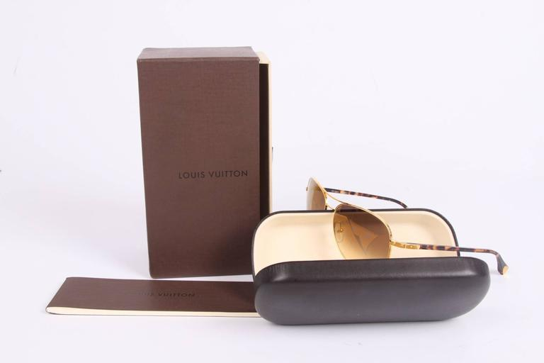 Stunning hand made pilot style glasses by Louis Vuitton; the Conspiration Pilote Sunglasses.  Crafted in gold-tone metal with dark brown tortoise arms. These arms have gold-tone detaling in the traditional Louis Vuitton trunk style.  The