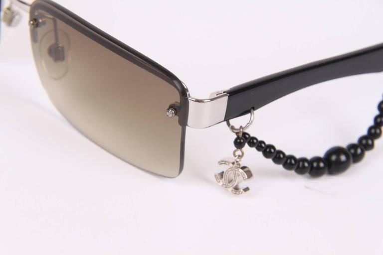 Charming pair of Chanel sunglasses with a silver-tone CC charm and a black string of beads on one of the temples.  The lenses are in a dégradé brown colour, the temples are crafted in black acetate and silver-tone accents. Different sizes of black