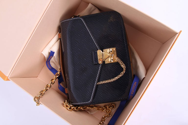 This is the Louis Vuitton Métis Mini, the lastest version from the fall/winter collection of 2017 in dark blue epi patent leather. Neat!!  The front, back and flap are crafted of dark blue epi patent leather. On top a natural coloured handle with a