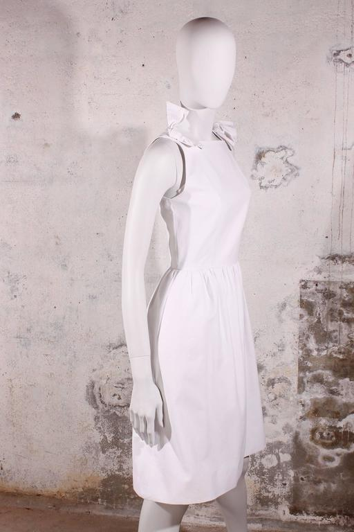 A perfect little white Chanel dress, with a bow on top of each shoulder.