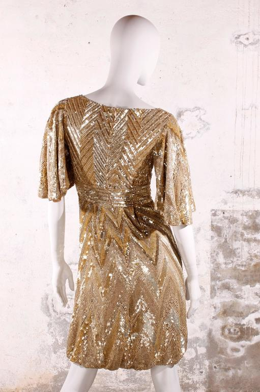 Très chique Elie Saab cocktail dress totally covered with golden sequins and beads in a zig-zag pattern. A festive eye-catcher!  Empire dress with a very low cut V-neck and short sleeves. Dress has knee-length and a balloon skirt.   A zipper on