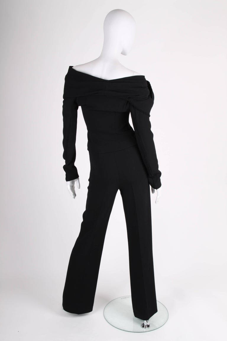 Donna Karan made this wonderful black suit! A wrap top and flared trousers.  The of-shoulder wrap top has hook closure on both sides, long sleeves, a large collar and is embellished with a XL flower on the right side. No lining.   The pair of